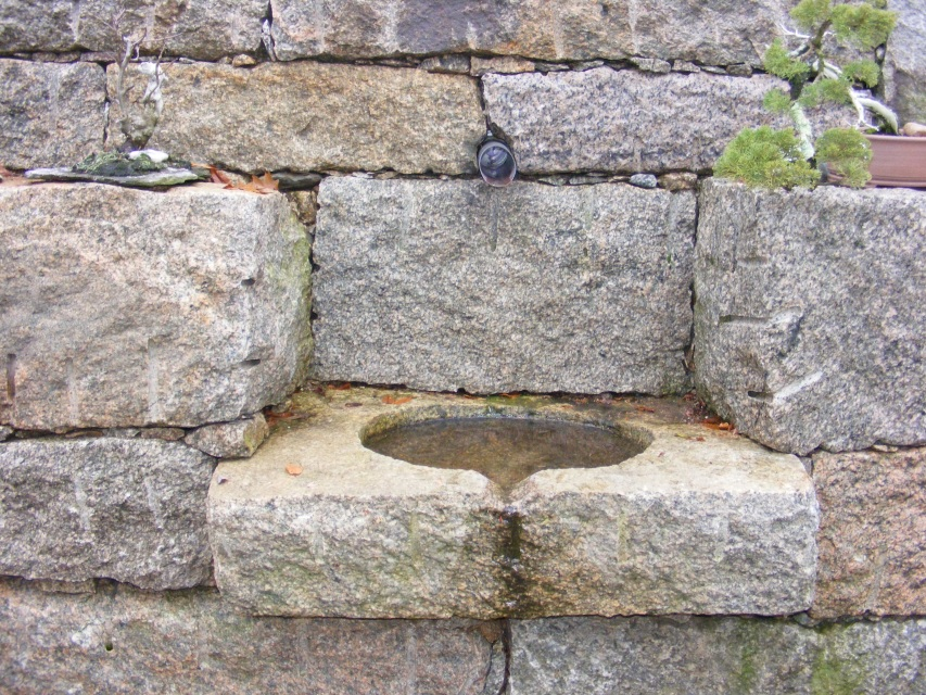 stone basin built into a retaining wall. Water from adownspout fills ...